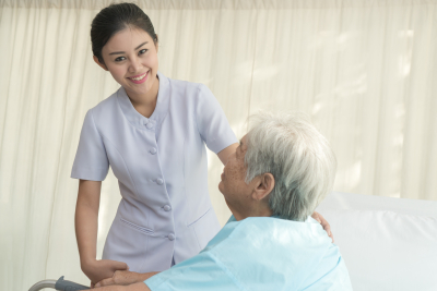 nurse assisting disabled senior woman