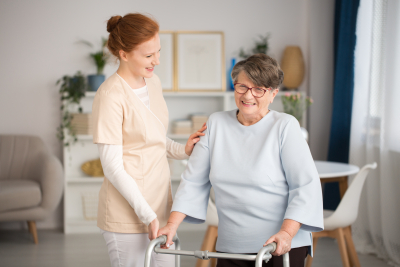 caregiver helping smiling senior woman with a walker