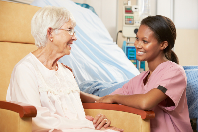 nurse walking to senior woman seated in chair