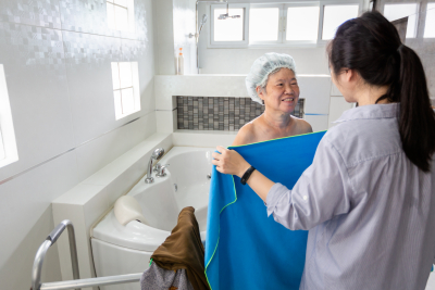 caregiver giving a clean towel to the senior woman