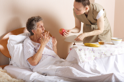 caregiver giving a fresh fruits to the senior woman at bed