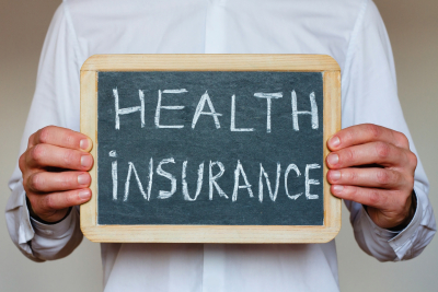 health insurance concept, text on chalkboard in hands of doctor