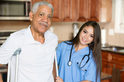 nurse giving care to senior man at home