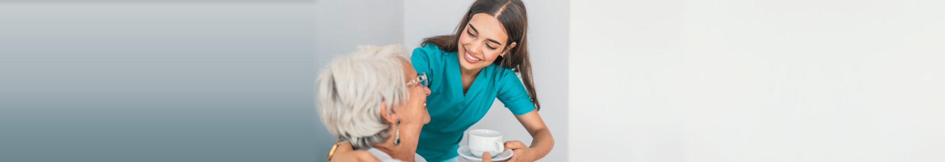 caregiver smiling while giving a cup of water